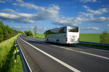 Bus traveling on the asphalt road along the green fields and alleys in the countryside