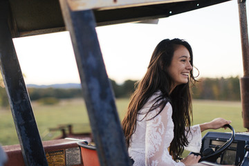Farm girl rides tractor on a late fall afternoon