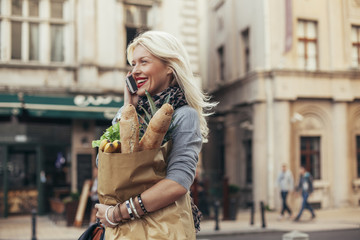 Beautiful Blonde Woman Making a Phone Call While Grocery Shopping