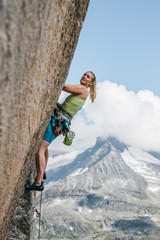 young sporty female rock climber climbing in the mountains