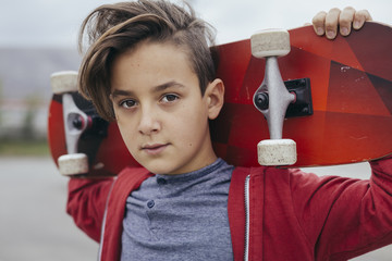 Boy skater posing with skateboard
