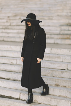 Woman in a black coat and hat walking down