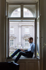 Man sitting at the window and working on a computer