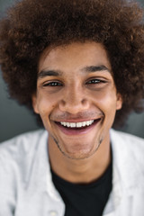 Portrait of a handsome young afro man over grey background
