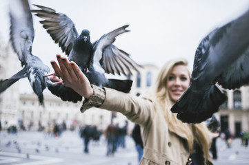 Young woman feeding pigeons in the city