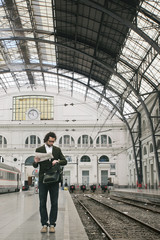 Young businessman holding newspaper checking the time waiting on train station