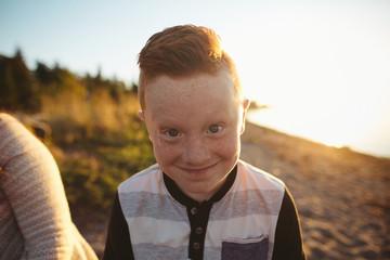Funny freckled boy making face toward camera