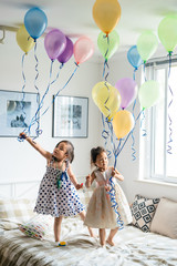 Girls playing with balloons in bedroom