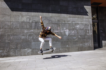 Young skater woman jumping with her skateboard in front dirty wall