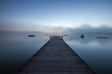 wooden dock on a lake in morning fog at sunrise