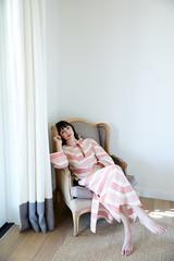 Portrait of woman relaxing in chair in bedroom
