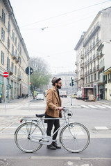 Young hipster walking with bicycle in the city