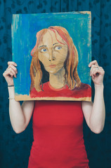 Woman holding a portrait of herself
