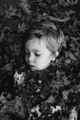 Black and white of little girl with eyes closed covered in leaves