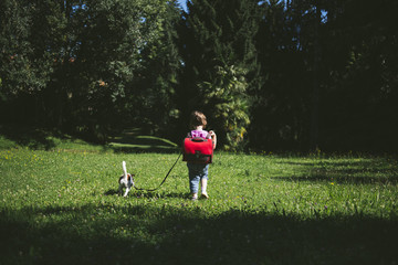 Schoolchild with backpack walking with a dog in the park