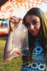 A young girl holding a prize fish at a carnival