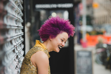 Young woman with curly purple hair laughs