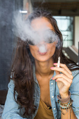 Beautiful tanned girl blowing cigarette smoke into the camera