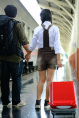 Woman and man hold hands walk in train station go travel,blur background