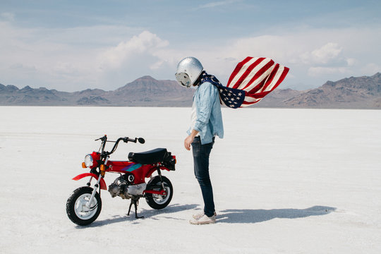 portrait of young male wearing american flag while riding motorcycle through desert salt flat