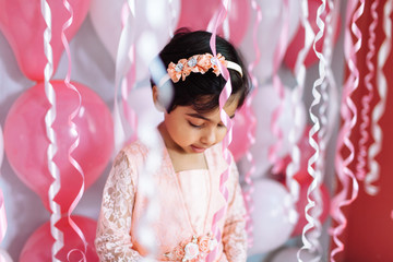Cute little girl surrounded by birthday party streamers
