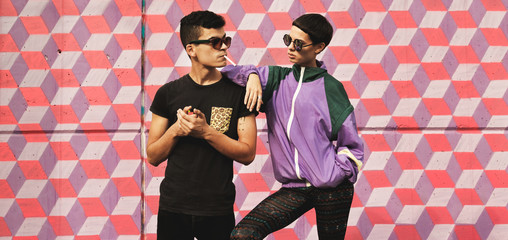 Wild kids/Hip young couple in front of colorful pattern wall in hip/retro /sporty outfit