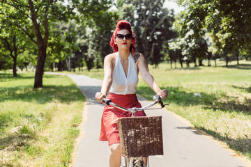 Young pin up woman riding a bicycle