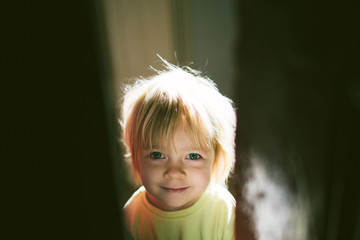 Backlit image of cute girl child opening a door wearing a yellow jumper