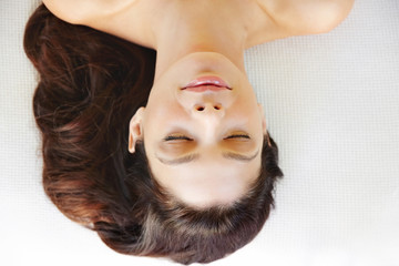 Beautiful woman relaxing on massage table for facial spa treatment