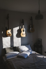 Bedroom with bed, guitars and basses