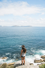 A girl wearing a hat stands on a cliff overlooking the blue ocean