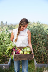 Woman holding a wood box in garden with fresh picked vegetables