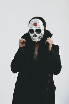 young woman wearing a  Mexican sugar skull mask