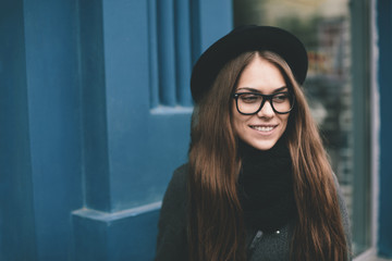 Happy young woman  with black hat on the street