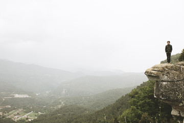 Young modern man observing beautiful landscape on the top of the mountain