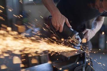 Blacksmith grinding in workshop