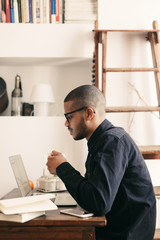 Side view of a latin man working with laptop at home office