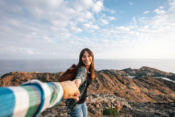 Happy woman holding her boyfriend hand on a beautiful landscape