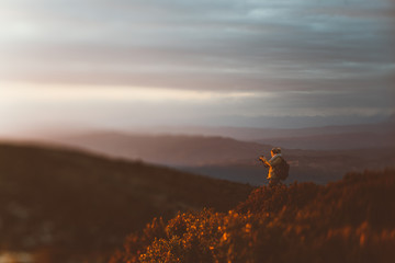 Woman photographing mountains at sunset