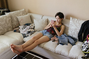 Young Asian girl using smartphone at home
