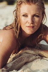 Blonde Woman Lying on a Sandy Beach