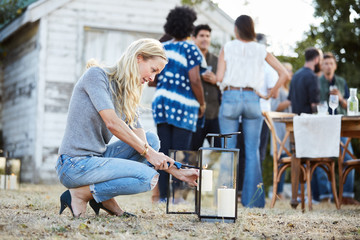 Woman lighting a candle at a Farm to Table Dinner Party