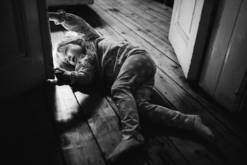 Candid black and white image of a young girl lying on the floor peering round a door