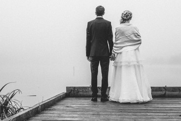 back view of a bridal couple holding hands on a jetty at a lake in foggy landscape