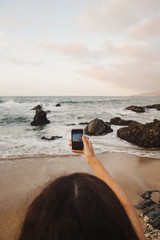 Woman at beach at sunset, taking picture with mobile phone