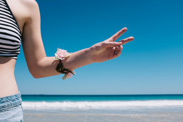 Girl at beach making peace sign with her fingers