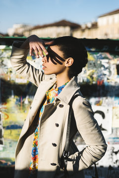 Young styling black woman covering her eyes from sun