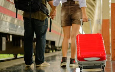 Woman and man hold hands walk in train station go travel
