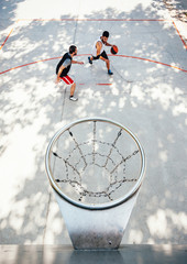 Aerial view of two young basketball players training on a outdoors court
