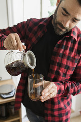 A middle aged man pouring a coffee